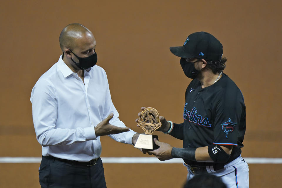 Miami Marlins CEO Derek Jeter, left, presents Miami Marlins shortstop Miguel Rojas a trophy for being chosen as the Marlins' nominee for the Roberto Clemente Award, during a ceremony before the start of a baseball game between the Marlins and the Philadelphia Phillies, Saturday, Sept. 12, 2020, in Miami. (AP Photo/Wilfredo Lee)