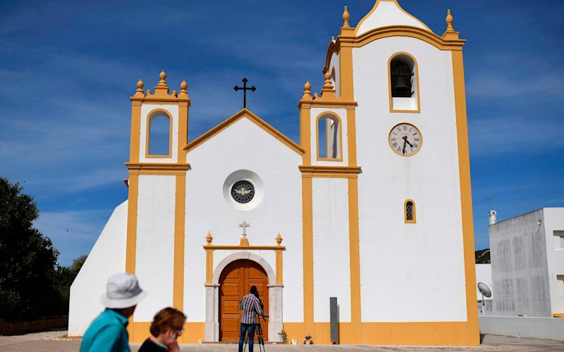 People walk past a church in Praia da Luz where a memorial mass for Madeleine McCann will be celebrated on May 3, 2017, on the 10th anniversary of her disappearance - Credit: AFP
