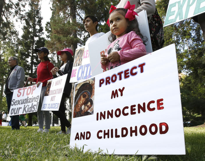 Angelie Reyes, 4, joins her family from Anaheim Hills to protest proposed changes to sex education guidance for teachers, Wednesday, May 8, 2019, in Sacramento, Calif. The California State Board of Education is set to vote Wednesday on new guidance for teaching sex education in public schools. The guidance is not mandatory but it gives teachers ideas about how to teach a wide range of health topic including speaking to children about gender identity. (AP Photo/Rich Pedroncelli)