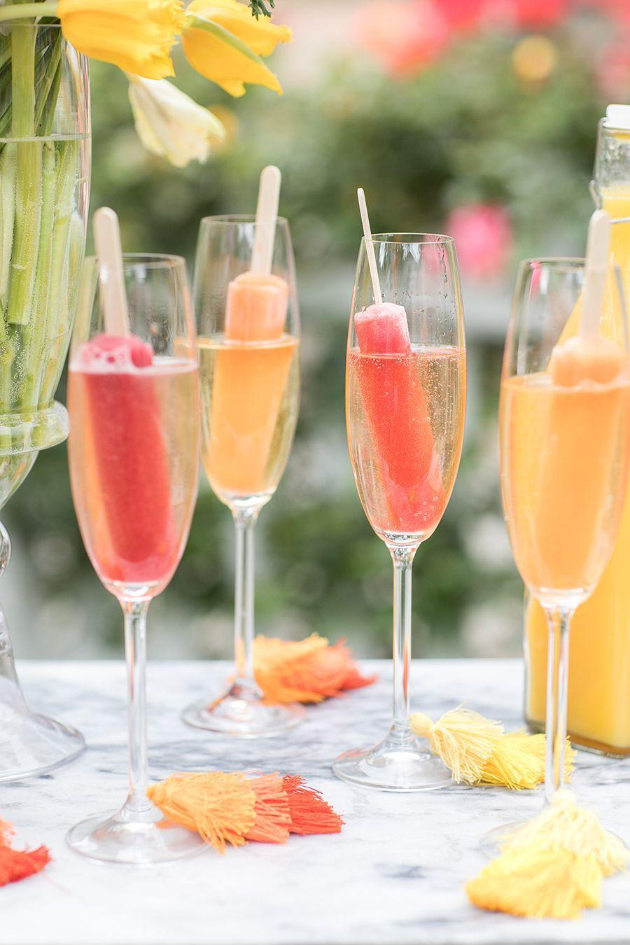 """<p>Freeze fruit juices into popsicles then stick them in champagne flutes. Just when you thought bubbly couldn't get any better. </p><p>See more at <a href=""""https://sugarandcharm.com/2018/05/a-college-graduation-bubbly-bar.html?section-2"""" rel=""""nofollow noopener"""" target=""""_blank"""" data-ylk=""""slk:Sugar and Charm"""" class=""""link rapid-noclick-resp"""">Sugar and Charm</a>.</p>"""