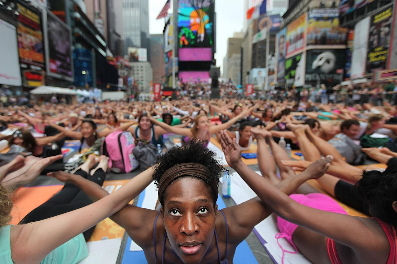 NEW YORK, NY - JUNE 21:  Bernice Acosta and other enthusiast perform yoga in Times Square during an event marking the summer solstice on June 21, 2011 in New York City.  Thousands of yogis will attend the free day-long event in Manhattan on the longest day of the year. (Photo by Mario Tama/Getty Images)