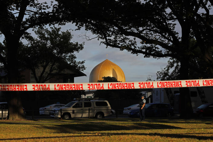 FILE - In this March 17, 2019, file photo, a police officer stands guard in front of the Masjid Al Noor mosque in Christchurch, New Zealand, where one of two mass shootings occurred. More than 60 survivors and family members will confront the New Zealand mosque gunman during the four-day sentencing starting Monday, Aug. 24, 2020. Twenty-nine-year-old Australian Brenton Harrison Tarrant has pleaded guilty to 51 counts of murder, 40 counts of attempted murder and one count of terrorism in the worst atrocity in the nation's modern history.(AP Photo/Vincent Yu, File)