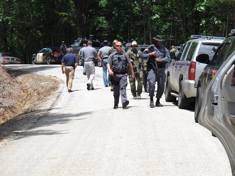 FBI agents and Mississippi state troopers prepare to search for a man charged with kidnapping a Tennessee mother and her three daughters and killing two of them, Wednesday, May 9, 2012 in Guntown, Miss.  The Mississippi man, Adam Mayes, 35, was added Wednesday to the FBI's 10 Most Wanted list. (AP Photo/Adrian Sainz)