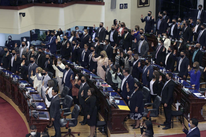 Ruling party New Ideas lawmakers are sworn-in at the Congress in San Salvador, El Salvador, Saturday, May 1, 2021. For the first time in three decades the traditional conservative and leftist parties have been sidelined by a resounding electoral defeat, clearing the way for President Nayib Bukele's party to help him advance his agenda. (AP Photo/Salvador Melendez)