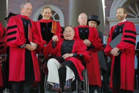 Former U.S. President George H. W. Bush (C) acknowledges the applause as he receives a honorary Doctor of Laws degree during the 363rd Commencement Exercises at Harvard University in Cambridge, Massachusetts May 29, 2014. Also pictured is fellow honorary degree recipient former New York mayor Michael Bloomberg (L). REUTERS/Brian Snyder