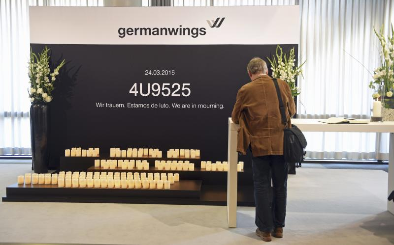 A Lufthansa shareholder signs a book of condolences for the victims of the Germanwings flight 4U9525 before the annual shareholders meeting in Hamburg, Germany