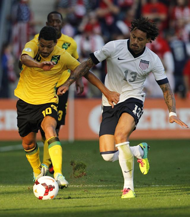 Jamaica midfielder Joel McAnuff (10) and U.S. midfielder Jermanie Jones (13) try to control of the ball in the first half of a World Cup qualifier soccer match at Sporting Park in Kansas City, Kan., Friday, Oct. 11, 2013. (AP Photo/Colin E. Braley)