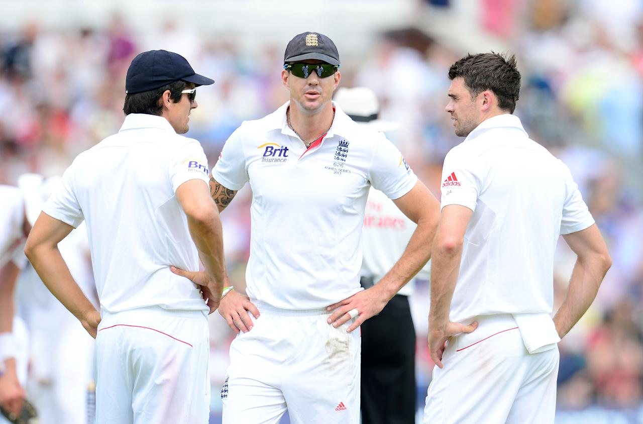 England's Alastair Cook, Kevin Pietersen and James Anderson confer as Australia's Chris Rogers makes 50 during day one of the Third Investec Ashes test match at Old Trafford Cricket Ground, Manchester.