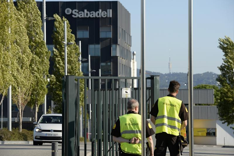 Security personnel stand at the entrance of the cooperative offices of Sabadell Bank (AFP Photo/Josep LAGO)