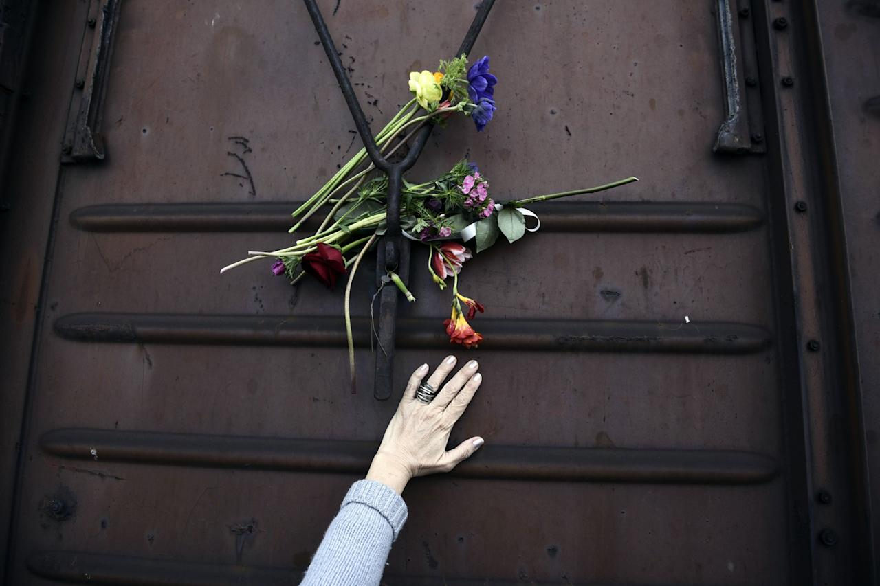 <p>A woman places flowers on a train wagon at the old train station in Thessaloniki, Greece, March 19, 2017. Residents of this northern Greek city visited the train station to mark the 74th anniversary of the roundup and deportation of its Jews to Nazi extermination camps during World War II. (Photo: Giannis Papanikos/AP) </p>
