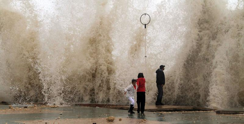 A man stands in front of towering water as high waves smash against a wall in the southern port city of Sidon, Lebanon, Sunday, Dec. 12, 2010. Heavy rain and fierce winds pummeled countries across the Middle East early Sunday, killing a woman in Lebanon, sinking a ship off Israel's coast and prompting Egypt to close its largest Mediterranean port. (AP Photo/Mohammed Zaatari)