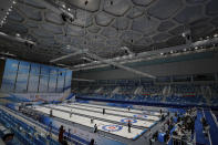 """Local team players compete in a curling competition during a test event for the 2022 Beijing Winter Olympics at National Aquatic Center, also known as the """"Water Cube"""" in Beijing, Thursday, April 1, 2021. Chinese capital holds 10 days test events for 2022 Beijing Winter Olympics in five different venues from April 1-10 and becomes the first city to hold both the Winter and Summer Olympics. (AP Photo/Andy Wong)"""