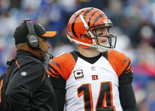 FILE - In this Sunday, Oct. 18, 2015, file photo, Cincinnati Bengals quarterback Andy Dalton (14) talks to head coach Marvin Lewis during the second half of an NFL football game against the Buffalo Bills in Orchard Park, N.Y. Dalton's 49-yard touchdown pass in the closing seconds of the 2017 season finale at Baltimore knocked the Ravens out of playoff contention and helped Lewis get a two-year extension in Cincinnati. (AP Photo/Bill Wippert, File)
