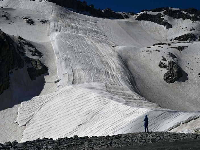 A man watches the huge geotextile sheets put on the Presena glacier near Pellizzano in Trentino, Italy, to delay snow melting on ski slopes, July 4, 2020.