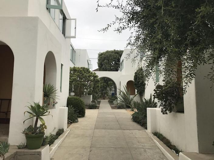 A series of elegant Modern arches painted in white surround a courtyard space studded with plants.