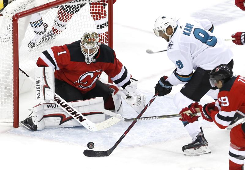 New Jersey Devils goaltender Keith Kinkaid (1) and center Travis Zajac (19) defend against San Jose Sharks left wing Evander Kane (9) during the third period of an NHL hockey game, Sunday, Oct. 14, 2018, in Newark, N.J. (AP Photo/ Noah K. Murray)