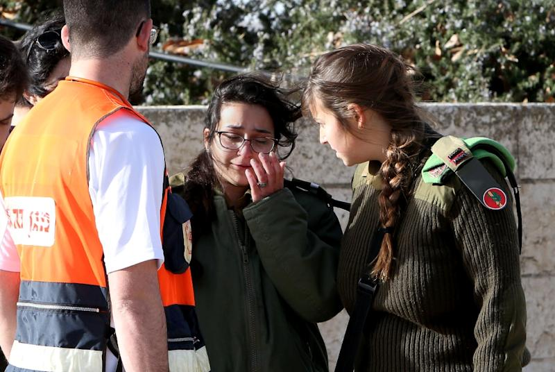 Israeli medical personnel assist an Israeli soldier who was an eye witness to the attack in Jerusalem, on January 8, 2017 (AFP Photo/Gali Tibbon)