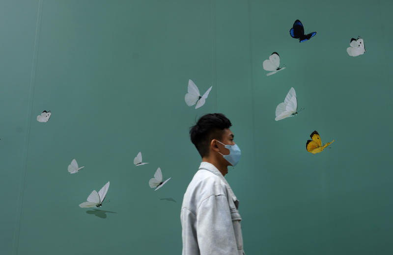 A man wearing face mask walks past a shop at a down town street in Hong Kong Wednesday, March 25, 2020. For most, the coronavirus causes only mild or moderate symptoms, such as fever and cough. But for a few, especially older adults and people with existing health problems, it can cause more severe illnesses, including pneumonia. (AP Photo/Vincent Yu)