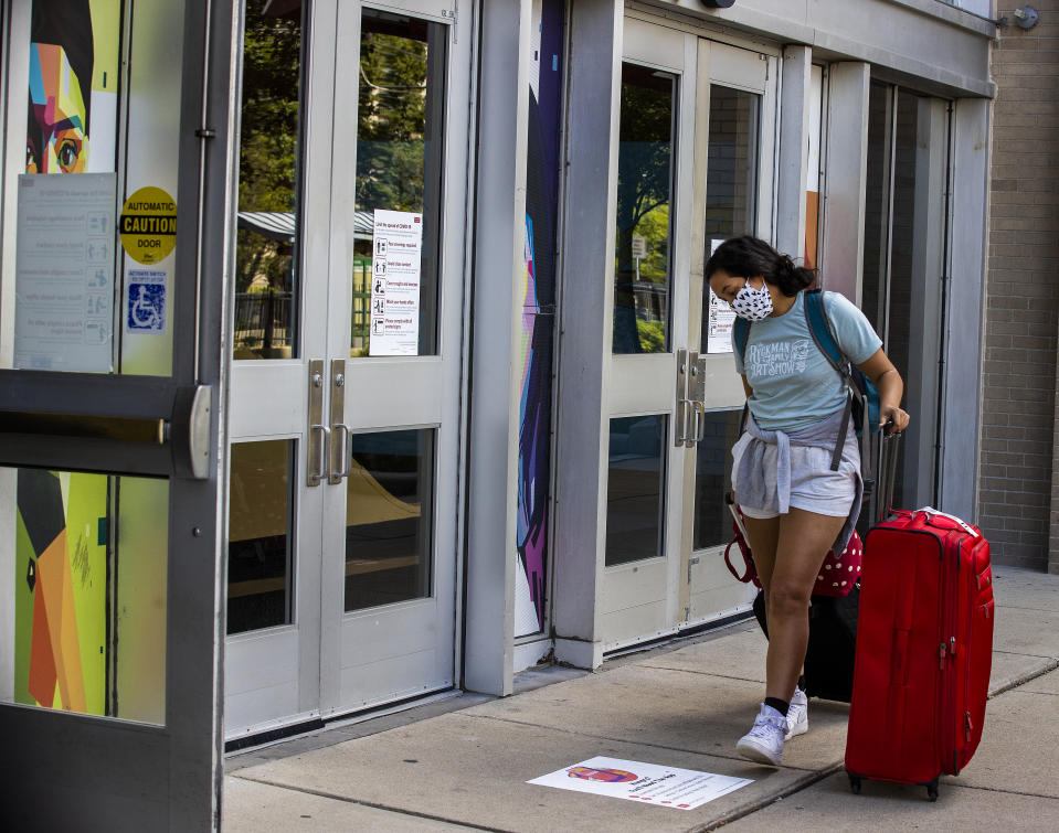 A Boston University student moving into a dorm reads a sign about coronavirus protocols on Aug. 18. (Stan Grossfeld/the Boston Globe via Getty Images)