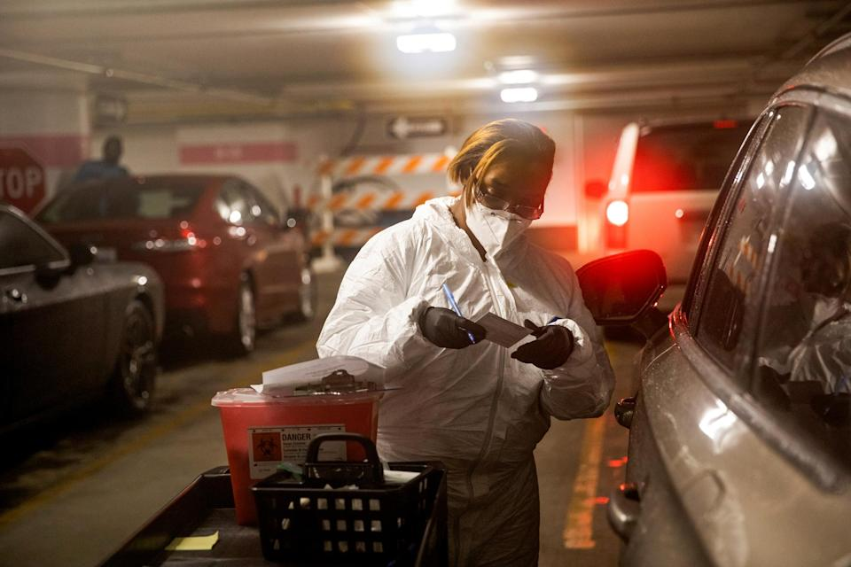 IMage: A nurse speaks with a person in their vehicle waiting to receive the Covid-19 vaccine in Detroit on Jan. 15, 2021. (Emily Elconin / Reuters file)