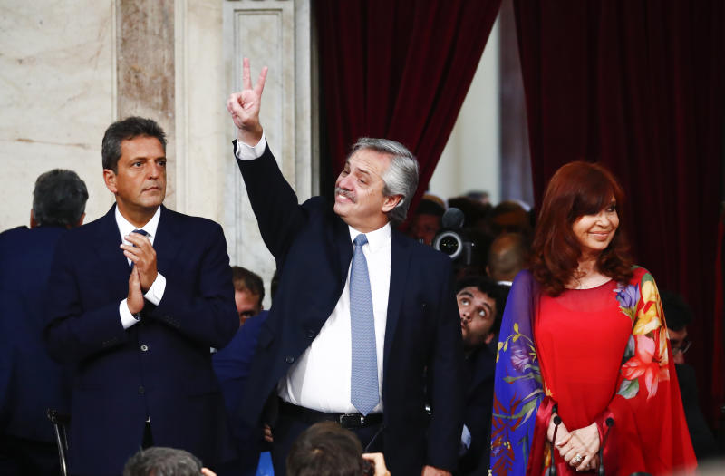 Argentina's President Alberto Fernandez, center, flashes a victory sign alongside Vice President Cristina Fernandez, right, and Lower House of Congress President Sergio Massa, as he arrives at Congress to open the 2020 session in Buenos Aires, Argentina, Sunday, March 1, 2020. (AP Photo/Marcos Brindicci)