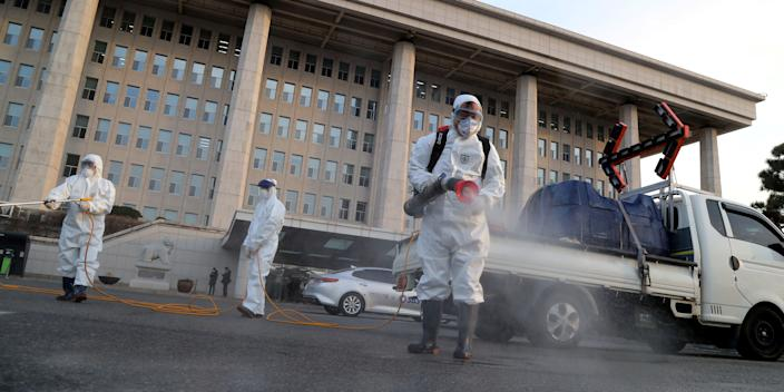 Employees from a disinfection service company sanitizing outside the National Assembly in Seoul, South Korea.