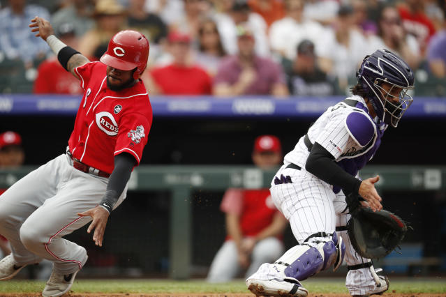 Cincinnati Reds' Phillip Ervin, left, scores on a single hit by Scooter Gennett as Colorado Rockies catcher Tony Wolters fields the throw in the second inning of a baseball game Sunday, July 14, 2019, in Denver.(AP Photo/David Zalubowski)