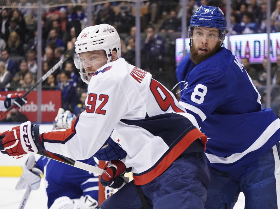 Washington Capitals center Evgeny Kuznetsov (92) works against Toronto Maple Leafs defenseman Jake Muzzin (8) during the first period of an NHL hockey game Tuesday, Oct. 29, 2019, in Toronto. (Hans Deryk/The Canadian Press via AP)