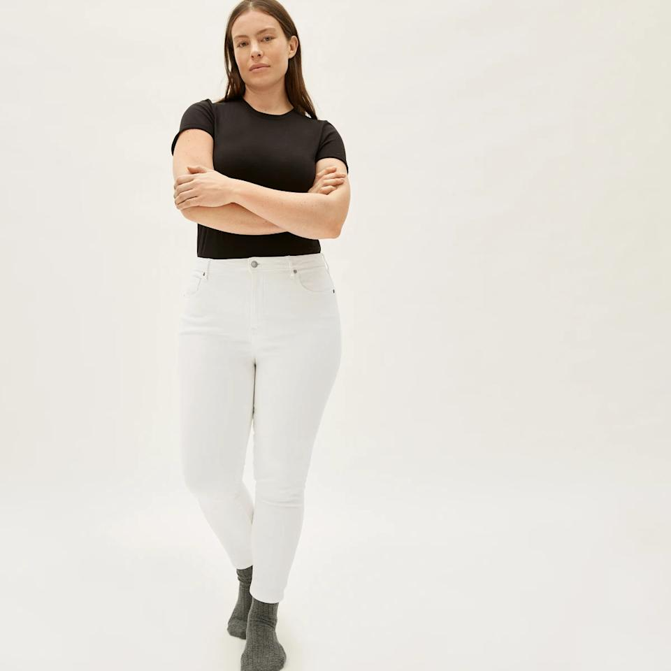 Model wears The Curvy Authentic Stretch High-Rise Skinny Jean in white with a black T-shirt. Image via Everlane.