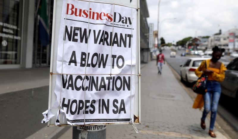 A woman walks past newspaper billboards during the coronavirus disease (COVID-19) outbreak in Johannesburg
