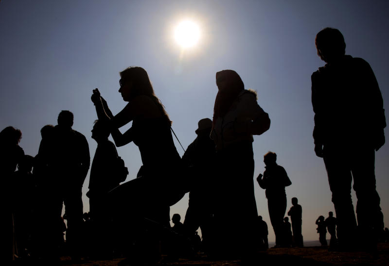 FILE - This Jan. 4, 2011 file photo shows tourists taking pictures at the site of the Giza Pyramids, Egypt during a partial solar eclipse. Solar eclipses typically attract tourists who travel around the world to remote places to witness the celestial phenomenon. Australia is expecting 50,000 visitors for a Nov. 14 solar eclipse that will be visible from the Cairns-Port Douglas area in Queensland. (AP Photo/Amr Nabil, file)
