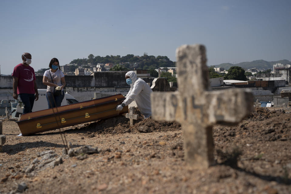 Rodrigo Bessa, left, attends the burial of his mother Edenir Rezende Bessa, who is suspected to have died of COVID-19, in Rio de Janeiro, Brazil, Wednesday, April 22, 2020. After visiting 3 primary care health units she was accepted in a hospital that treats new coronavirus cases, where she died on Tuesday. (AP Photo/Leo Correa)