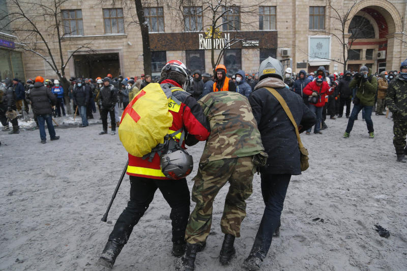 A wounded protester, center, is assisted by paramedics during clashes with police in central Kiev, Ukraine, early Wednesday, Jan. 22, 2014. Two people have died in clashes between protesters and police in the Ukrainian capital Wednesday, according to medics on the site, in a development that will likely escalate Ukraine's two month-long political crisis. (AP Photo/Sergei Grits)