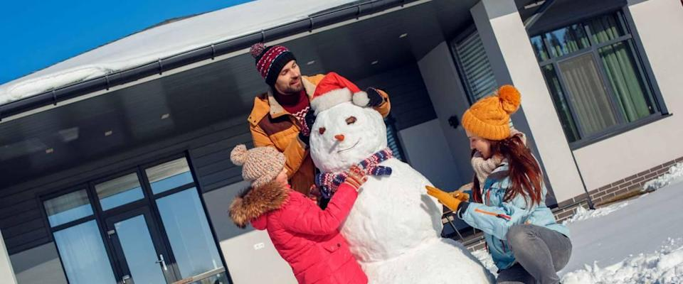 Family on a winter vacation spending time together outdoors standing near the house making snowman smiling concentrated