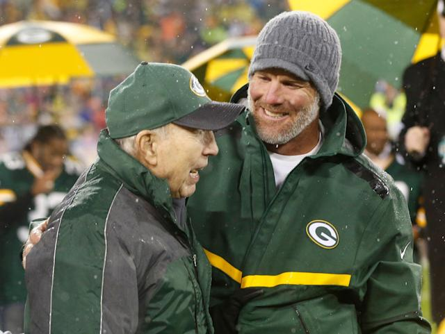 Brett Favre smiles with Bart Starr during a ceremony at halftime in 2015 when Favre's retired No. 4 and name were unveiled inside Lambeau Field. (AP)