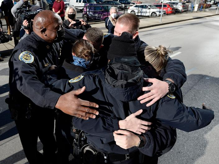 Nashville Metro Police Chief John Drake (left) and officers Amanda Topping and Michael Sipos and James Luellen and Brenna Hosey and James Wells spend a moment in a group hug after a press conference on Sunday, December 27, 2020 in Nashville, Tenn.