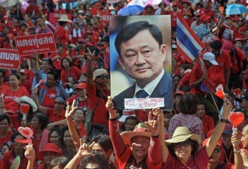 """""""Red Shirt"""" supporters hold a picture of fugitive former premier Thaksin Shinawatra during a demonstration in Bangkok on Saturday to mark the second anniversary of a deadly crackdown on street protests"""