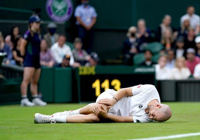 Adrian Mannarino holds his knee after slipping on Centre Court