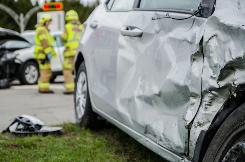 Close up on a car crashed during an accident with two firemen in background with firetruck during a day of summer