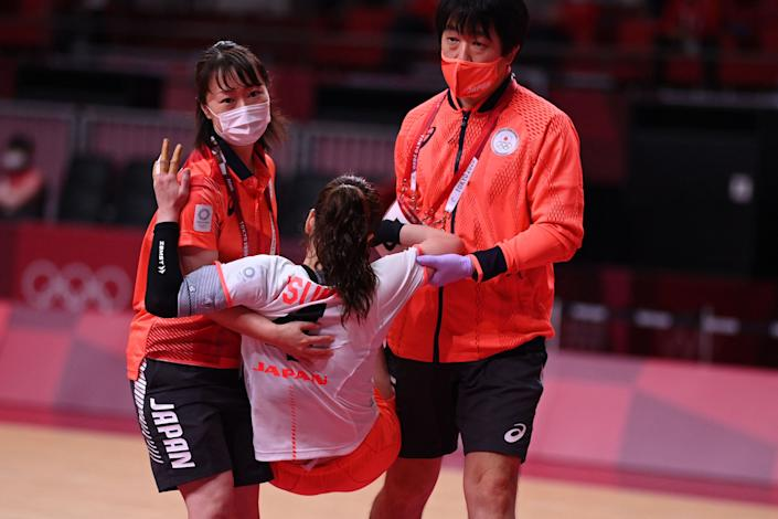 <p>Japan's right back Yui Sunami (C) is carried after being injured during the women's preliminary round group A handball match between Japan and Montenegro of the Tokyo 2020 Olympic Games at the Yoyogi National Stadium in Tokyo on July 27, 2021. (Photo by Daniel LEAL-OLIVAS / AFP)</p>
