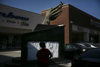 A shopper walks past a sculpture built in 1992 to honor Martin Luther King Jr. at a shopping mall named after Dr. King in the Watts neighborhood of Los Angeles, Wednesday, June 17, 2020. The Los Angeles community of Watts has long been associated with deadly and destructive rioting in 1965. This summer when widespread mostly peaceful protests for racial justice across the U.S. have been accompanied at times by vandalism and other crimes, Watts has been peaceful. One lawmaker says the residents learned long ago that it didn't pay to burn their own neighborhood. (AP Photo/Jae C. Hong)