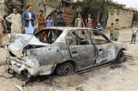 Locals view a vehicle damaged by a rocket attack in Kabul, Afghanistan, Monday, Aug. 30, 2021. Rockets struck a neighborhood near Kabul's international airport on Monday amid the ongoing U.S. withdrawal from Afghanistan. It wasn't immediately clear who launched them. (AP Photo/Khwaja Tawfiq Sediqi)