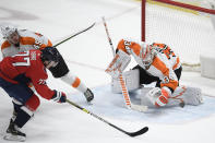 Philadelphia Flyers goaltender Alex Lyon (34) stops the puck against Washington Capitals right wing T.J. Oshie (77) during the second period of an NHL hockey game, Saturday, May 8, 2021, in Washington. Flyers defenseman Cam York is at top left. (AP Photo/Nick Wass)