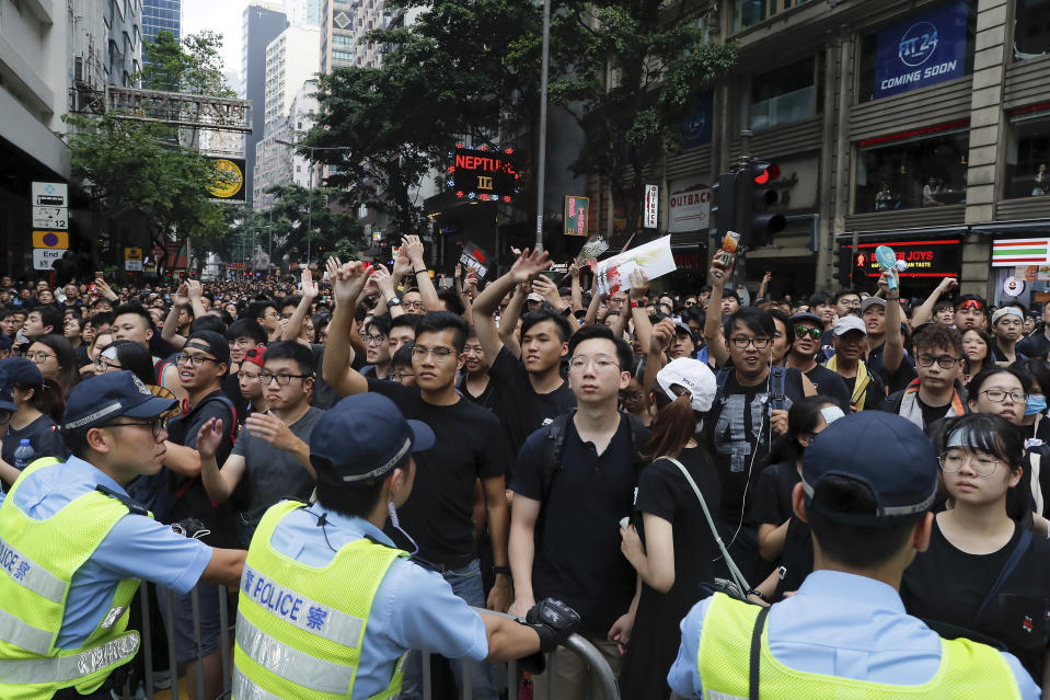 Policemen stand guard behind the barricades as tens of thousands of protesters march through the streets continuing to protest an extradition bill, Sunday, June 16, 2019, in Hong Kong. Hong Kong residents Sunday continued their massive protest over an unpopular extradition bill that has highlighted the territory's apprehension about relations with mainland China, a week after the crisis brought as many as 1 million into the streets. (AP Photo/Kin Cheung)
