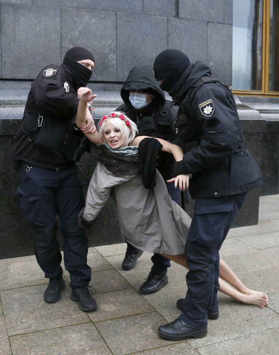 "Police detain an activist from Ukrainian female rights organization ""Femen"" on the International Day for the Elimination of Violence against Women as she protested naked in front of the Presidential Office in Kyiv, Ukraine, Wednesday, Nov. 25, 2020. Writing on her chest reads ""Istanbul"". Femen is demanding the Ukrainian authorities to ratify the Istanbul Convention on the protection of women. (AP Photo/Efrem Lukatsky)"