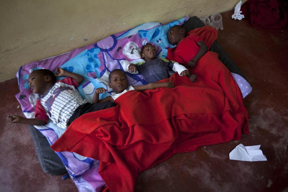 In this Nov. 13, 2013 photo, children lay on a worn mattress placed on the floor of the U.S.-based Church of Bible Understanding orphanage in Kenscoff, Haiti.. The orphanage is run by a Christian missionary group funded by the Olde Good Things antique store on Manhattan's Upper West Side. While many other orphanages also have failed the Caribbean country's new national standards, and conditions are far worse in some, the group's three-story building on the hilly outskirts of Port-au-Prince stands out because it's run by an organization with such an unusual, and successful fundraising operation. The failure to meet the standards would seem to contradict their financial position.(AP Photo/Dieu Nalio Chery)