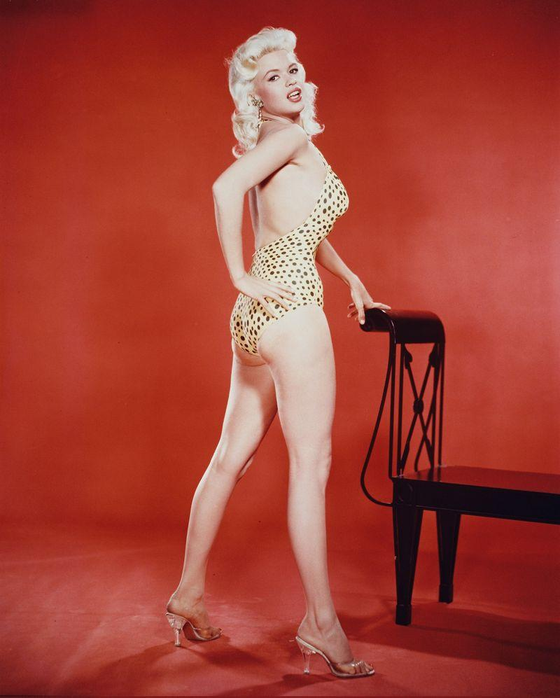 Full-length shot of Jayne Mansfield (1933-1967), US actress, wearing a leopard print swimsuit in a studio portrait, against a red background, circa 1955.