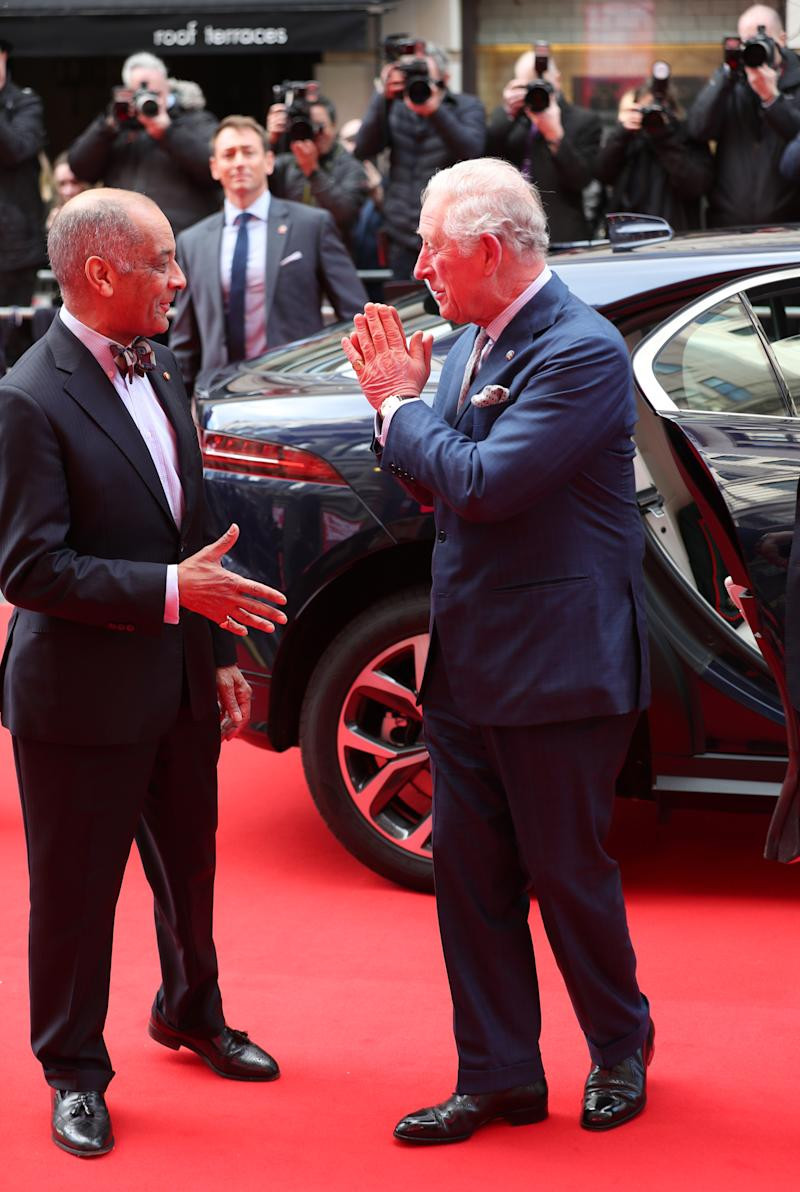 The Prince of Wales goes to shake the hand of Sir Kenneth Olisa, The Lord-Lieutenant of Greater London (left) before he changes to use a Namaste gesture, as he arrives at the annual Prince's Trust Awards 2020 held at the London Palladium.
