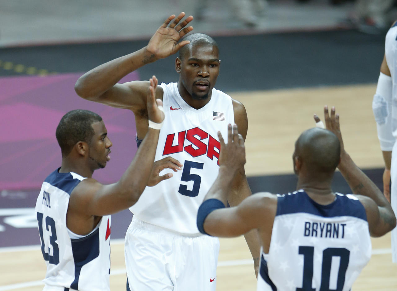 USA's Kevin Durant (5), Chris Paul (13) and Kobe Bryant (10) react during the first half of a preliminary men's basketball game against France at the 2012 Summer Olympics, Friday, July 27, 2012, in London. (AP)