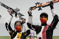 Yang Qian, left, and Yang Haoran, of China, celebrate after taking the gold medal in the mixed team 10-meter air rifle at the Asaka Shooting Range in the 2020 Summer Olympics, Tuesday, July 27, 2021, in Tokyo, Japan. (AP Photo/Alex Brandon)